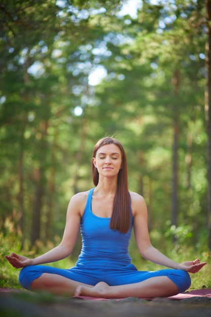 young-woman-sitting-outdoors-in-yoga-position_1098-1390